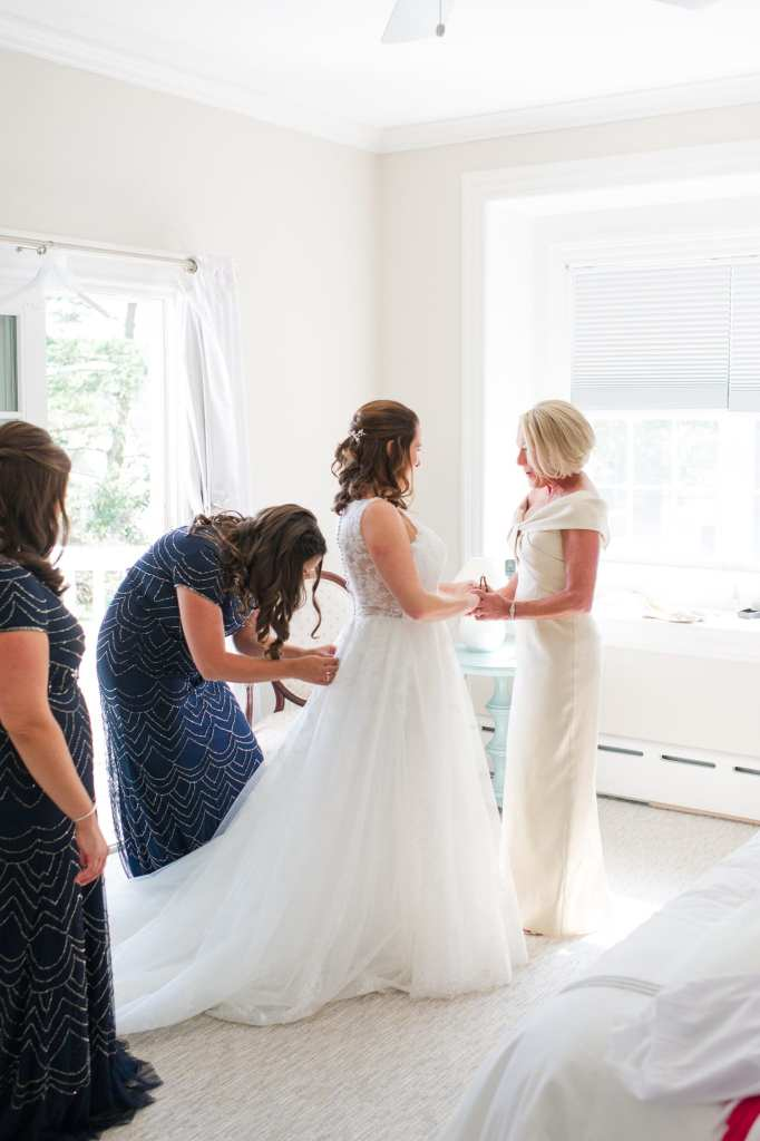 The bride being buttoned into her gown by her maid of honor while holding hands with her mother