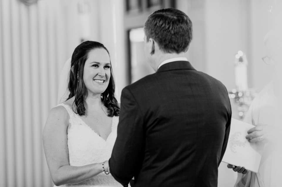 Black and white candid of the bride smiling during her vows