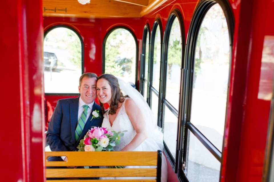 Bride and groom smiling while seated on their trolley transportation