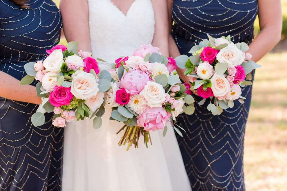 Bride and her bridal party in navy blue beaded gowns by Adrianna Papell, focus in on their bouquets of flowers in various shades of pink by Wallflowers