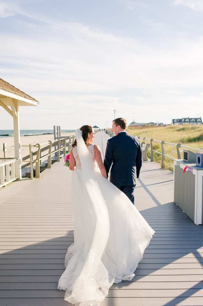 Bride and groom walking away from the camera while holding hands and looking at one another on the boardwalk