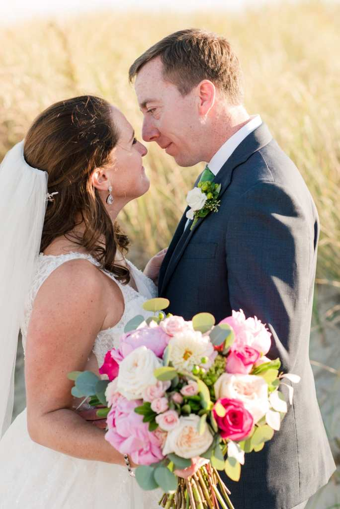Bride and groom smiling at one another, nose to nose