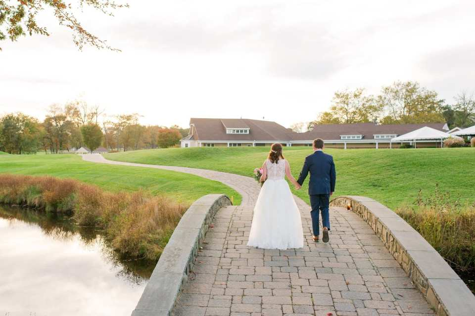 Bride and groom walking away from the camera, hand in hand, over a bridge at their Sprink Lake Golf Club Wedding