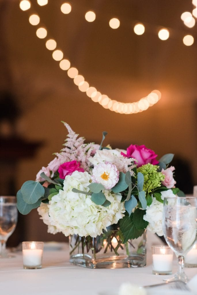 Low floral arrangements on reception tables consisting of hydranges, roses and assorted pink florals by Wallflowers
