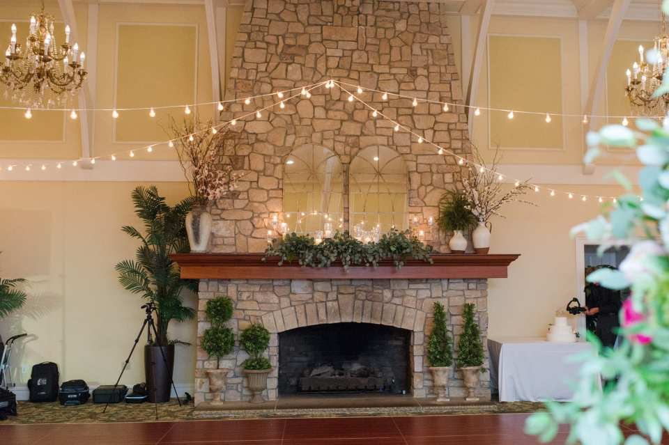 The stone floor to ceiling fireplace inside the reception ballroom at this Spring Lake Golf Club Wedding