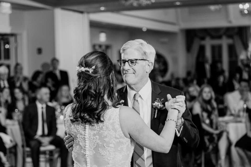 Black and white candid photo of the bride dancing with her father