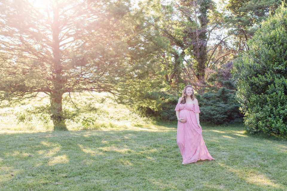 Wide angle shot of the mother to be walking in her flowing pink off the shoulder gown, cradling her pregnant belly, amongst the foliage at Rutgers Gardens in these New Jersey Maternity Photos