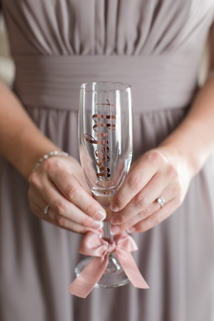 A member of the bridal party holding a custom champagne flute