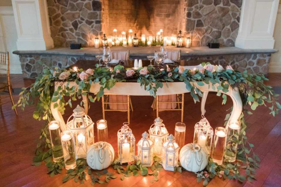 Sweetheart table decorated in greenery and peach roses, lanterns, candles and white pumpkins by the Bloomery Flower Studio in these Ryland Inn Wedding Photos