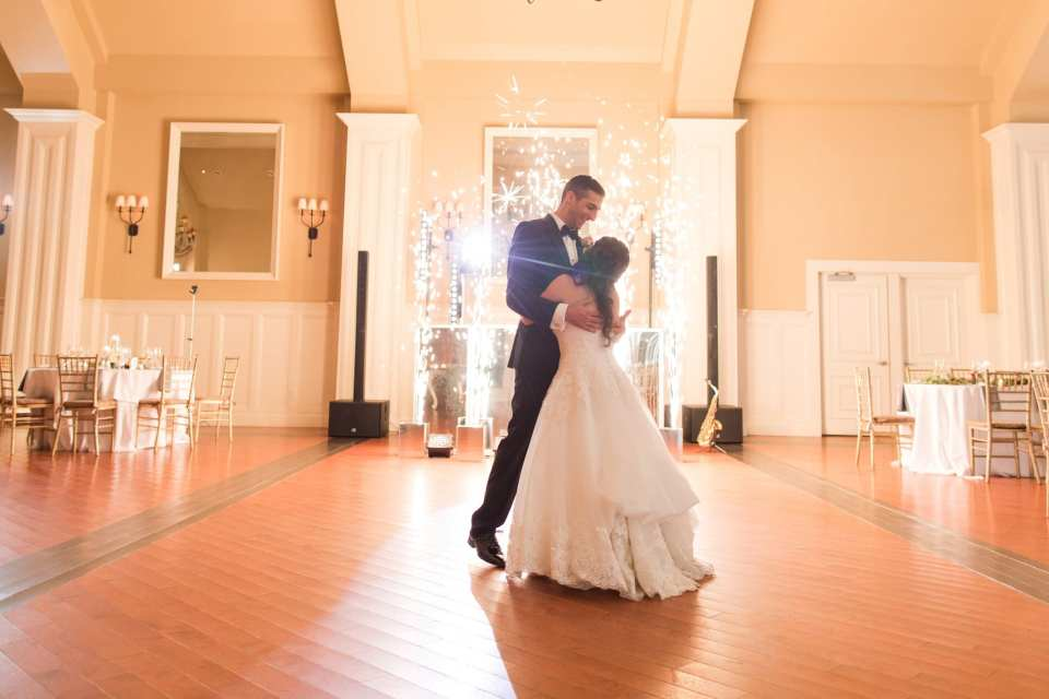 The bride and groom dance in the grand ballroom of the Ryland Inn in front of fireworks