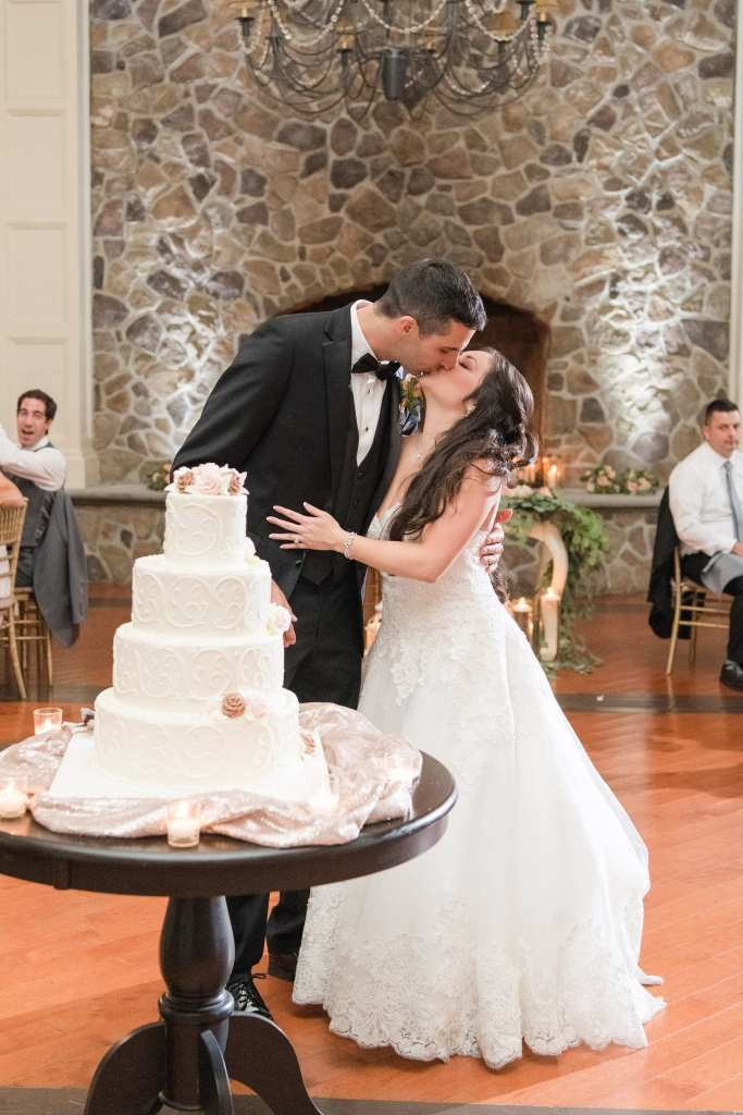 The bride and groom kiss behind their four tier white embossed wedding cake by Palermos in these Ryland Inn wedding photos