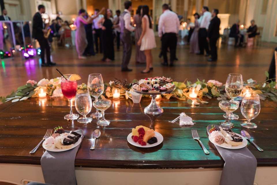 Reception shot with sweetheart table in foreground, desserts at the places of the bride and groom