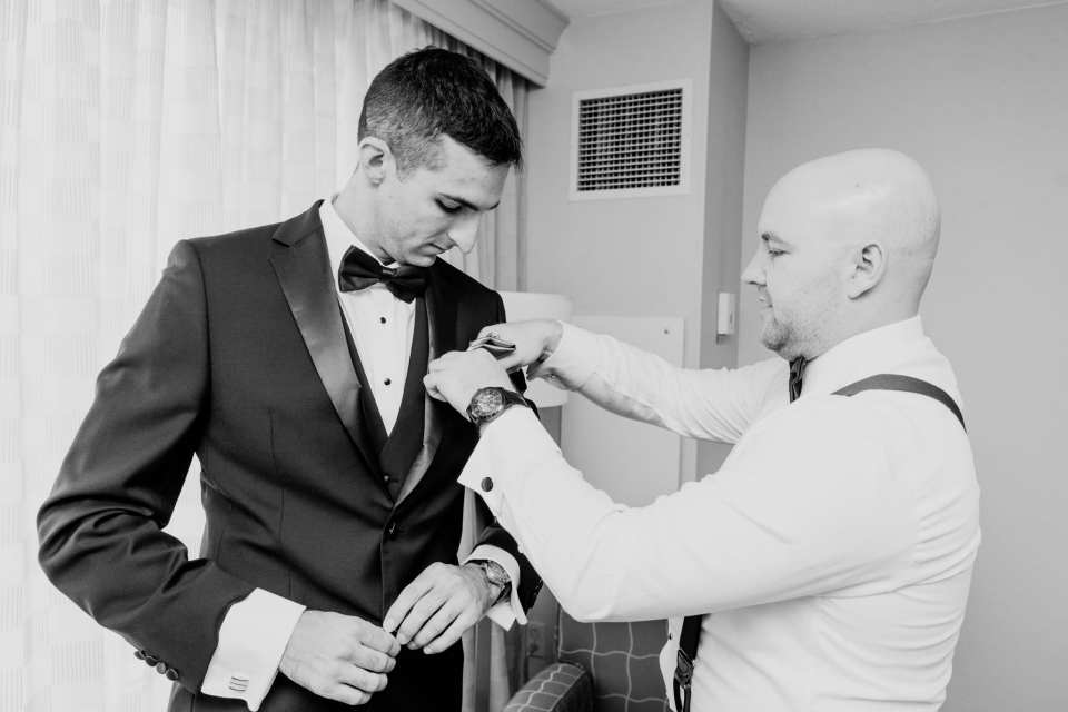 Black and white photo of the groom being helped into his Calvin Klein tuxedo by a groomsman