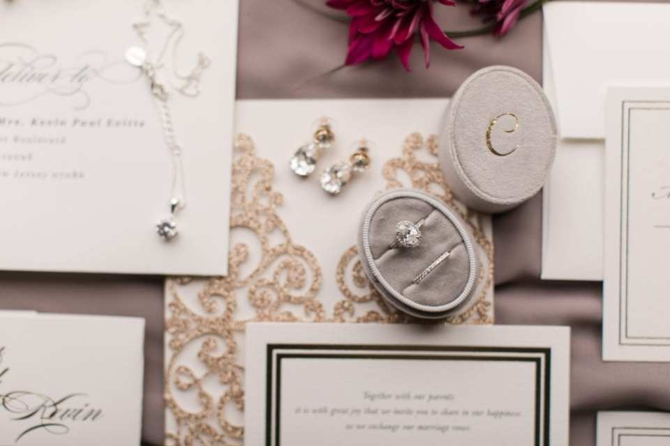 Close up of wedding invitation suite by Minted on display with wedding jewelry and florals