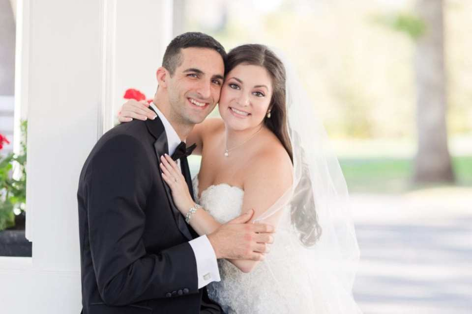 The bride leans into a sitting groom for a portrait