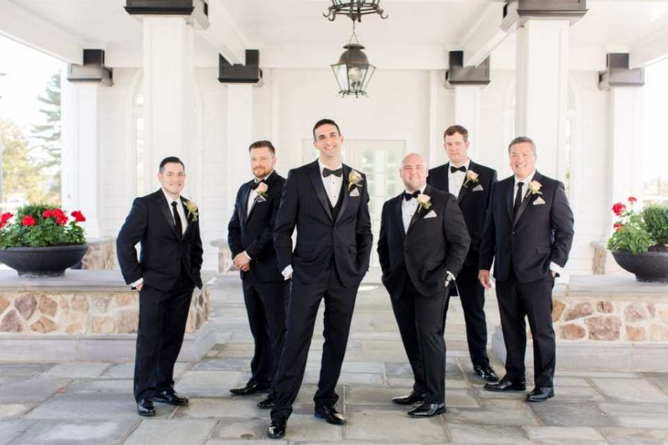 Formal photo of the groom and his groomsmen in their Calvin Klein tuxedos