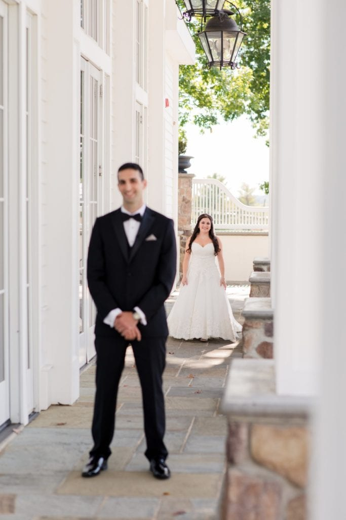 The bride comes up behind her groom in these first look photos in these Ryland Inn Wedding Photos