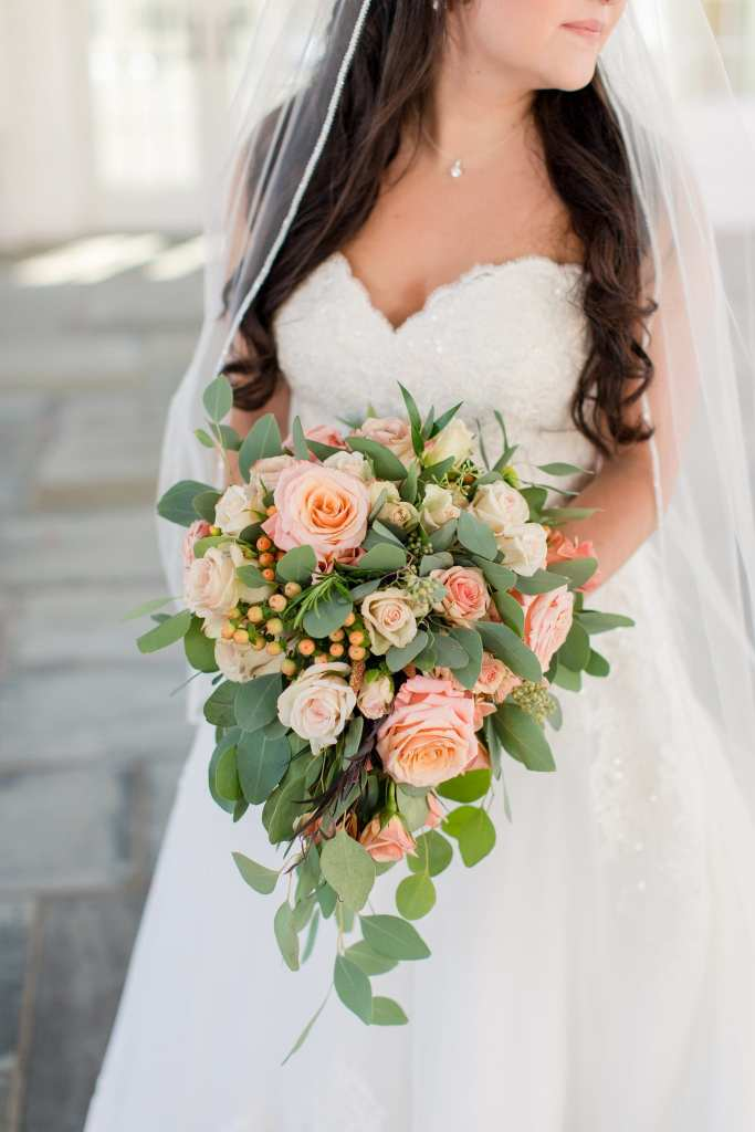 The bride in her Madison James gown and peach floral bouquet by the Bloomery Flower Studio