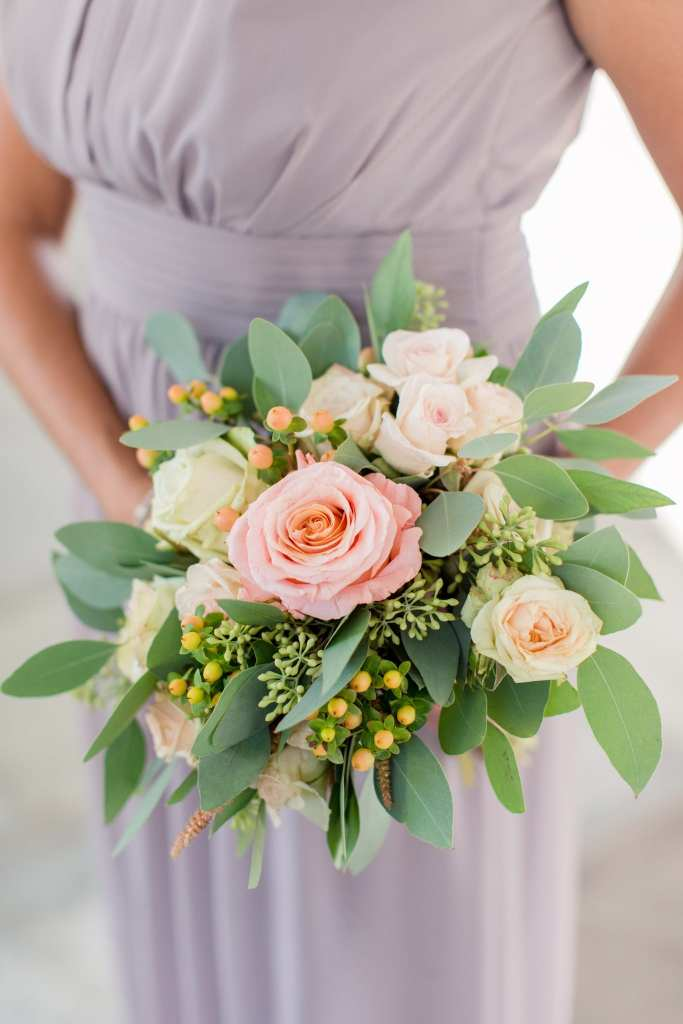 A bridal party member in her portobello gown by David's Bridal holds a bouquet of peach florals from Bloomery Flower Studio