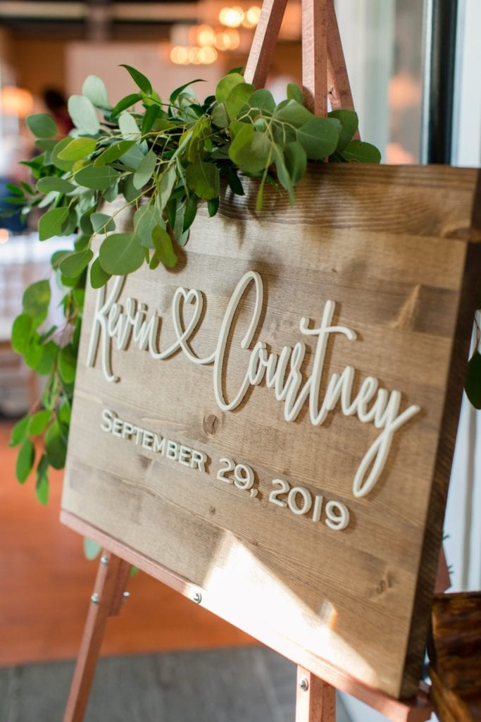 Custom wooden welcome sign at the entrance to the wedding