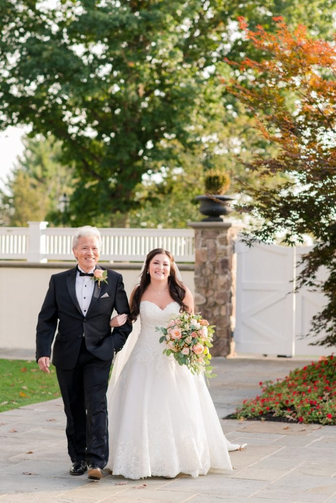 The bride in her Madison James wedding gown being walked down the aisle by her father