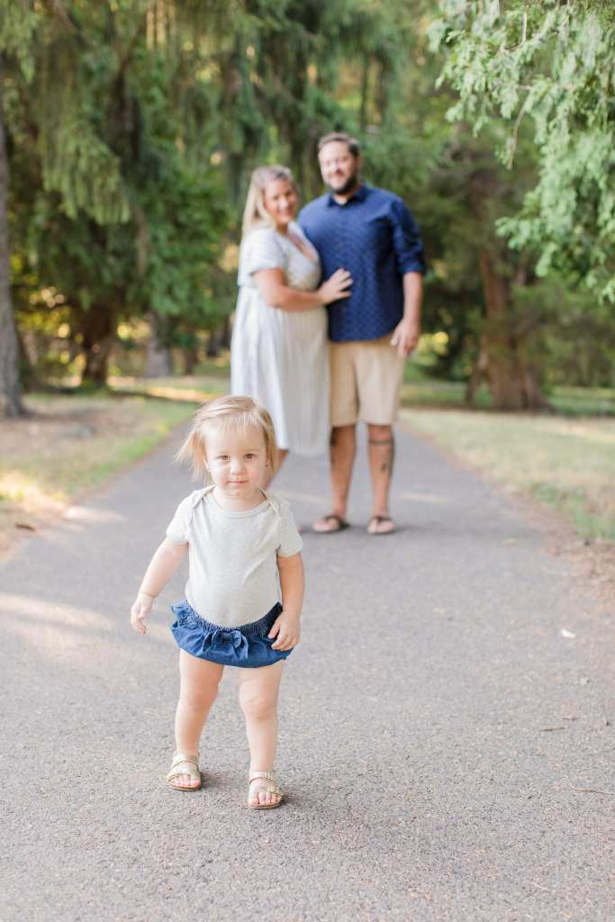 Mom and Dad arm in arm in the background looking on as toddler walks ahead in focus of front-line healthcare worker photos