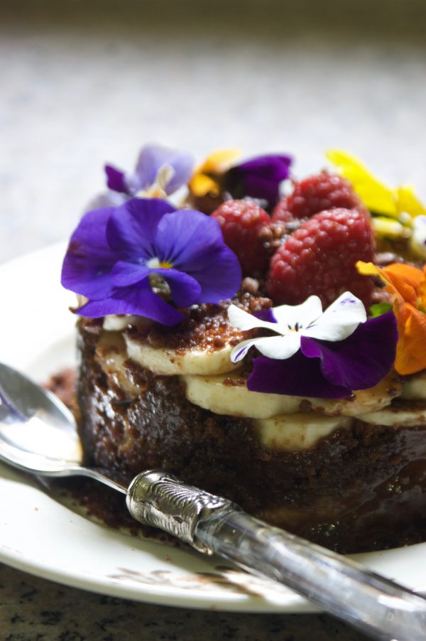 Bizcocho de chocolate frutas pistachos y flores