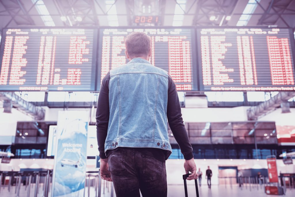 man at airport looking at boarding and flight schedules
