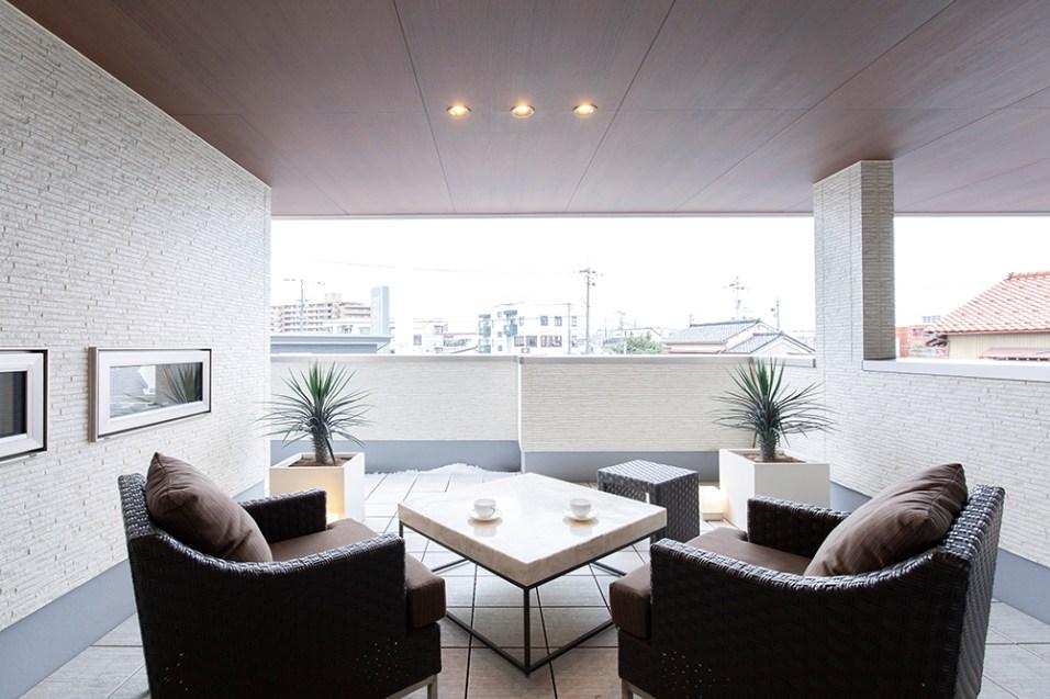多世帯にも対応したモデルハウス「IMAGE」。エネルギーの見える化を実現した家庭用エネルギー管理システム「HEMS(ヘムス)」を採用し、ウォールナットの無垢材の床材を用いたLDKなど、未来型のテクノロジーと自然素材の上質な心地良さを、見て・触れてご体感いただけるモデルハウスとなっている。上の写真は2階のバルコニーに設けられたアウトドアリビング。深い軒によって、強い日差しや雨の日にも、屋外での寛ぎの時間をお過ごしいただける。腰かけた際に、周囲の視線を遮りつつ景観を確保する塀の高さも絶妙だ