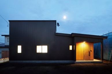 見た目は2階建て?と思う外観だが、実は平家建て。シックな黒い外壁にレッドシダーの外壁材を使った玄関まわりが好対照で印象的な住宅