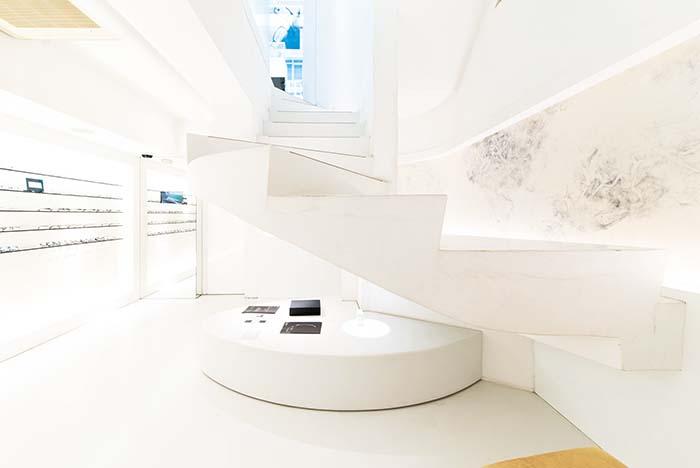 螺旋階段を下りた地下1階のメンズアイウェアのフロアでは、程良く閉じた心地の良い空間でメガネ選びをお愉しみいただける。右手の壁には越前和紙が配されて、白い壁面に美しい陰影を添える。メンズラインの「ジャポニスム」の全ての商品をご覧いただける