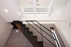 スチールの格子からは太陽光が優しく降り注ぐ階段エントランス。1階と2階を緩く繋げており、住まい全体が明るく風が通り抜ける