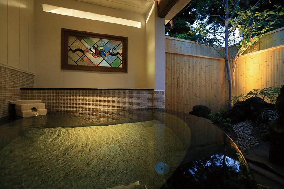温泉露天付・特別室「72 番」のお部屋の源泉かけ流し露天風呂。御影石とモザイクタイルがレトロな雰囲気を醸し出し、大正浪漫溢れるお風呂となっている