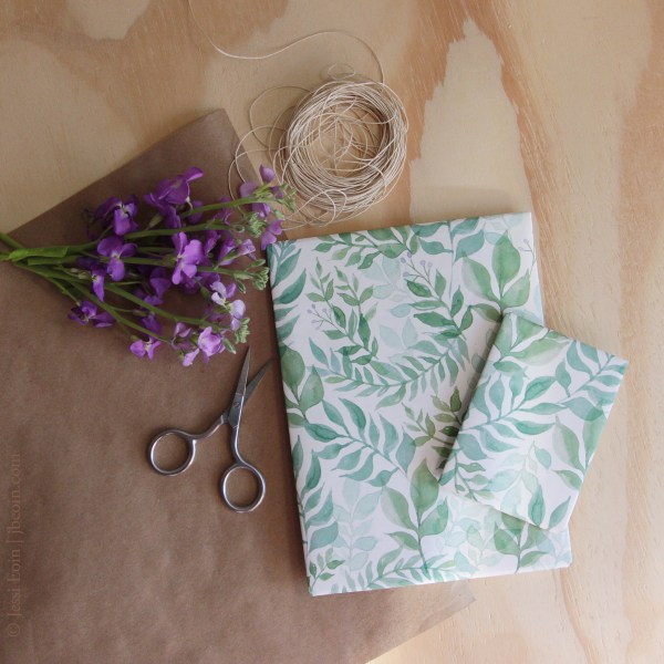 A styled photo of gift wrap options showing two paper options: plain brown Kraft paper and a green and white botanical paper that has a watercolor effect. The photo is styled with twine, purple stock flowers, and a small pair of silver scissors.
