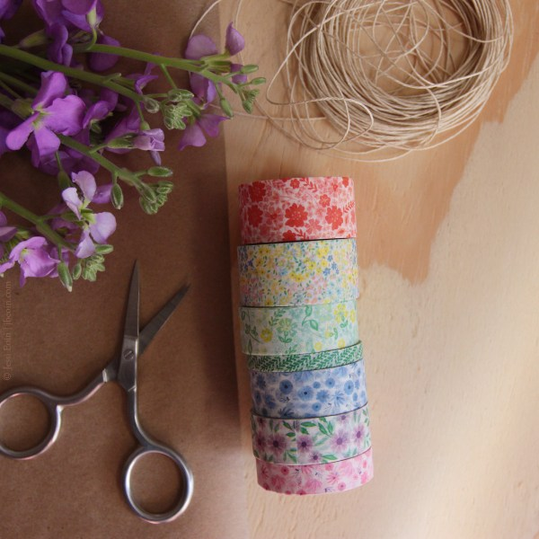 A styled photo of several rolls of colorful washi tape next to the twine, kraft paper, scissors, and flowers. The washi tapes come in seven color and pattern options. One is a reddish floral pattern; the next is a multi-color floral pattern with pinks, yellows, and blues; the next is a multi-color floral pattern with greens and yellows; the next is a thin, green leaf pattern; the next is a blue floral pattern; the next is a purple floral pattern with green leaves; the last one is a pink floral pattern.