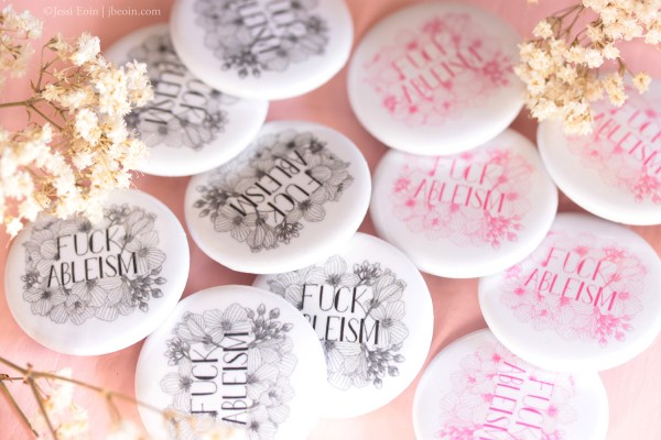 A photo showing the Fuck Ableism buttons both in the black and white design and in the pink and white design. The design in both colors is hand lettered in all caps, and the text is surrounded by an illustration of the cuckooflower. The photo here is showing a handful of the buttons on a pink background with some dried baby's breath around the buttons.