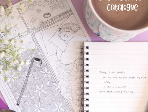 """The cover of the catalogue shows a photo of a purple background showing an open notebook with a short amount of writing on the paper, as well as a black Faber Castell pen on it, a 6 inch by 8 inch print of my piece Beloved, a small pair of purple paper cards, baby's breath flowers, a silver spoon, and a mug of hot chocolate in a pretty, abstract floral/botanical design in greens and pinks. On the spoon, there is a reflection of my hand outstretched to say hi, and on the paper, there is written a short poem: """"Today, I am grateful/ for the way the sun kisses my desk/ softly/ in the cool morning/ warm touch waking my day."""""""
