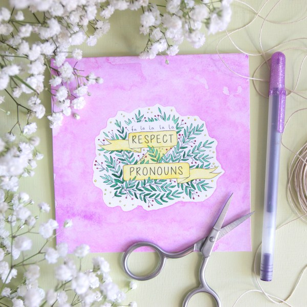 "A styled photo of a square, 5 inch by 5 inch, purple watercolor cards resting on a green background and surrounded by baby's breath flowers, a purple gel pen, some twine, and a small pair of silver scissors. The cards have a green, red, and yellow design of bright leaves and berries intertwining with a yellow banner with text that reads, ""Fa La La La La Respect Pronouns."" The purple paint on the card has a lovely watercolor effect with the paint blooming in some spots."