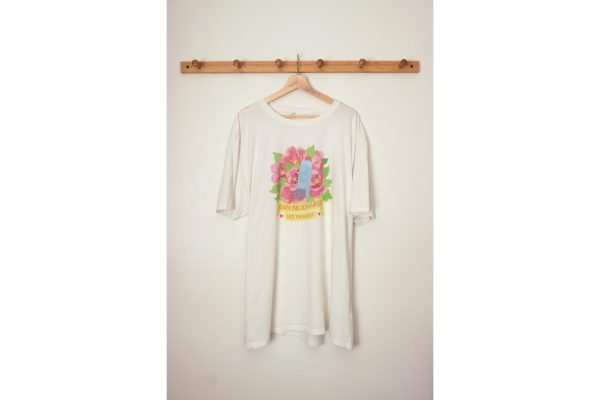 A photo of the shirt hanging on a wooden hanger hung on a wooden coat rack against an off-white wall.