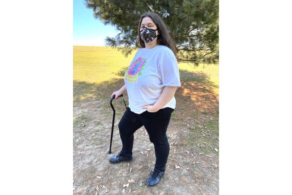 A second photo of Jessi modeling the shirt outdoors, smiling at the viewer from behind their unicorn Vogmask and standing with their cane and their hand in their pocket, proudly and visibly disabled. The shirt's colors are vibrant, and the shirt fits well and slightly loose, without being or looking too baggy, ending just past Jessi's butt. A white tank top's straps are just barely visible under the shirt.