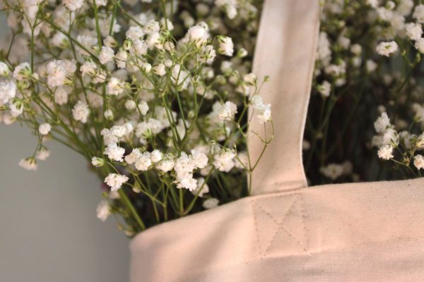 """A close up photo of the tote bag showing the attachment of the handle to the bag in an """"X"""" shape."""