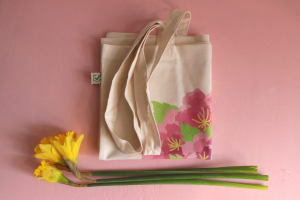 A styled photo of the tote bag folded up and resting on a pink background with a trio of bright yellow daffodils underneath it.