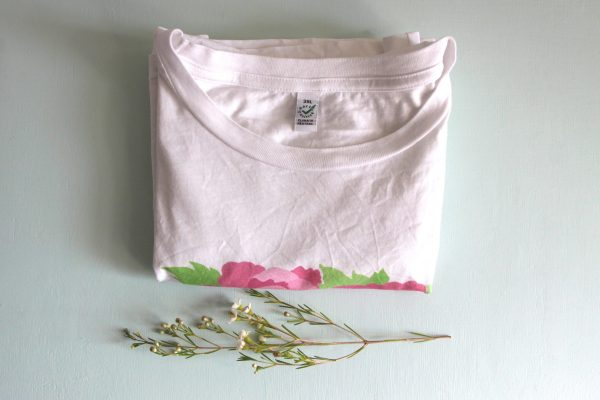 A photo of the folded shirt showing the collar and tag, which has a 3XL on it and info that labels it as Earth Positive and Climate Neutral.
