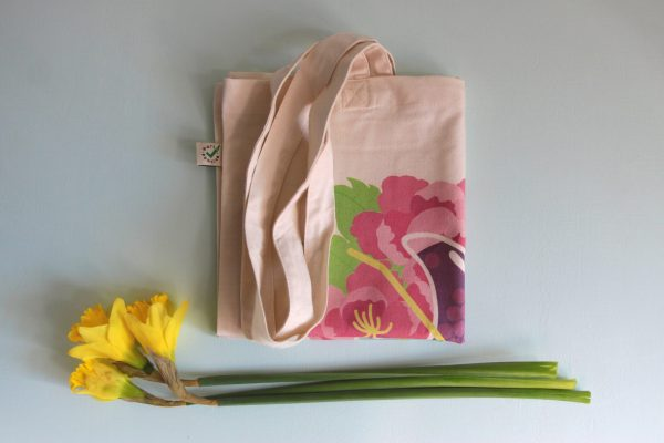 A styled photo of the tote bag folded up and resting on a blue background with a trio of bright yellow daffodils underneath it.
