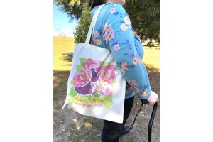 A photo of Jessi modeling the bag outdoors while wearing a blue, floral top and black pants, using a black cane. The bag is over their shoulder and has a bunch of fresh flowers in it. The size of the bag is fairly large and goes from about mid-back on Jessi to just below their butt.