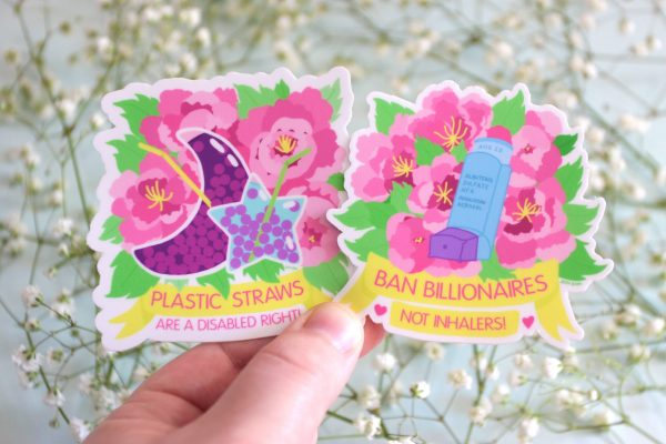 """A photo of Jessi's hand holding up two stickers: the """"Ban Billionaires, Not Inhalers!"""" design, and another design called """"Plastic Straws Are a Disabled Right!"""" The Inhalers design is of a colorful floral design behind a blue and purple inhaler that has the label """"Albuterol Sulfate HFA Inhalation Aerosol"""" and the expiration date """"Aug 20"""" on it. The floral design shows several big, pink peonies with yellow stamens and bright green leaves. Underneath the design is a yellow banner with pink text on it that reads, """"Ban Billionaires, Not Inhalers!"""" in all caps and two pink hearts on either side. The Straws design is of a colorful floral design behind some whimsical, moon and star shaped bubble tea drinks with flexible plastic straws in them. The moon shaped drink is purple with red-purple bubbles and a yellow straw, and the star shaped one is a pale blue with purple bubbles a green straw. The floral design shows several big, pink peonies with yellow stamens and bright green leaves. Underneath the design is a yellow banner with pink text on it that reads, """"Plastic Straws Are a Disabled Right!"""" in all caps."""