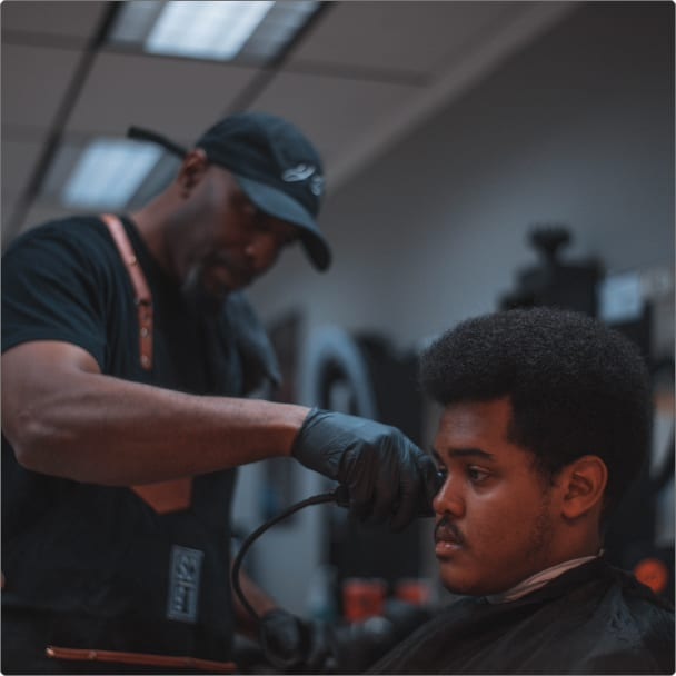 Man with cap cutting afro hair