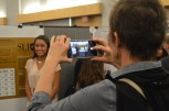 Service Learning Initiative for Community Engagement in Sociology (SLICES) attendees snap photographs of Alyssa Medina.