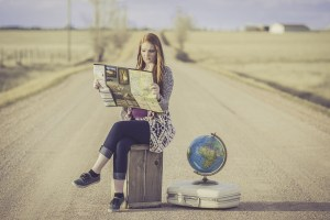 A young woman holding a map, sitting in the middle of a wide road, a globe and a suitcase next to her