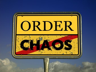 "A yellow sign with two words - ""order"" and ""chaos"", the latter one is crossed out"